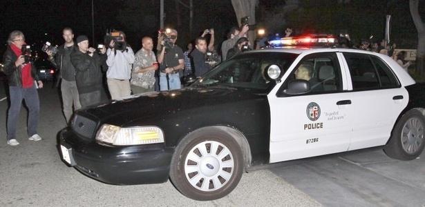 Polícia chega na casa de Charlie Sheen, em Los Angeles, que estava cercada de jornalistas e fotógrafos (9/3/11). Ao fazer busca por armas de fogo que pudessem violar um mandado judicial contra ele, a polícia encontrou apenas balas e um fuzil antigo