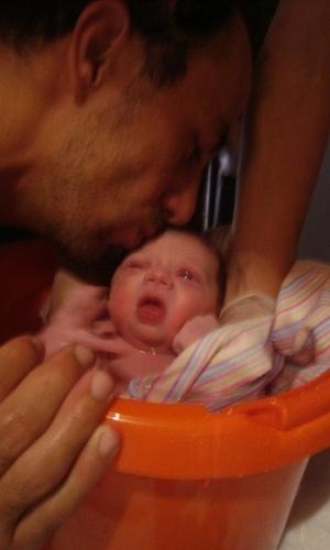 Paschoal Feola, marido da filha de Ana Maria Braga, beija a filha Joana quando ela toma banho de balde após nascer (3/2/2011)