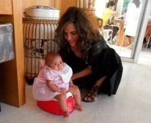 Maria, filha da apresentadora Ana Maria Braga, segura a filha Joana enquanto a menina está sentada em penico (10/5/2011)