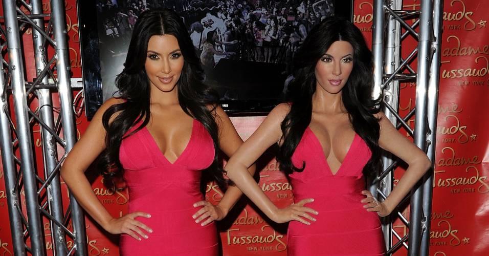 Com um vestido idêntico, a socialite Kim Kardashian (esq.) posa ao lado de sua figura de cera no museu Madame Tussauds de Nova York (1/7/2010)