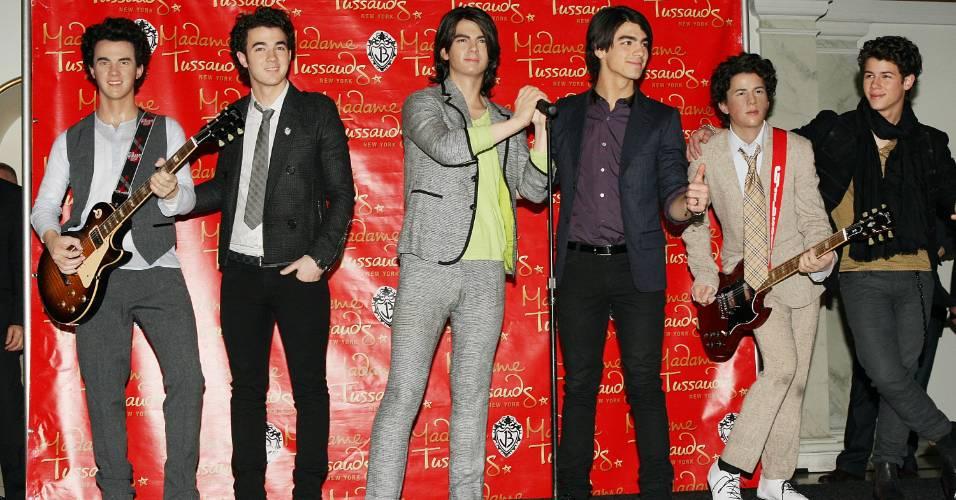 Jonas Brothers posam ao lado de suas figuras de cera no museu Madame Tussauds de Nova York (12/2/2009)