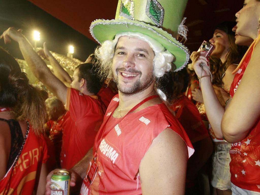 Usando chapéu e peruca, o ator Murilo Benício assiste desfile das campeãs no Sambódromo carioca (20/2/2010)