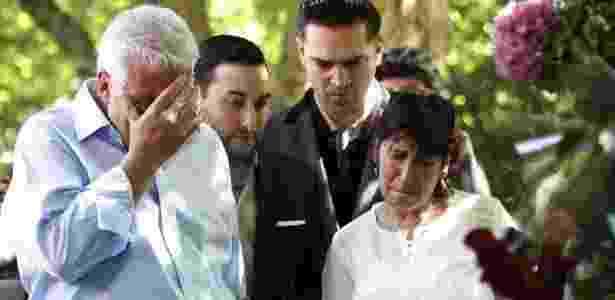 Os pais de Amy Winehouse, Mitch e Janis Winehouse, olham os presentes deixados pelos fãs em frente à casa da cantora em Londres e lamentam a morte da filha (25/7/2011) - Luke Macgregor/Reuters