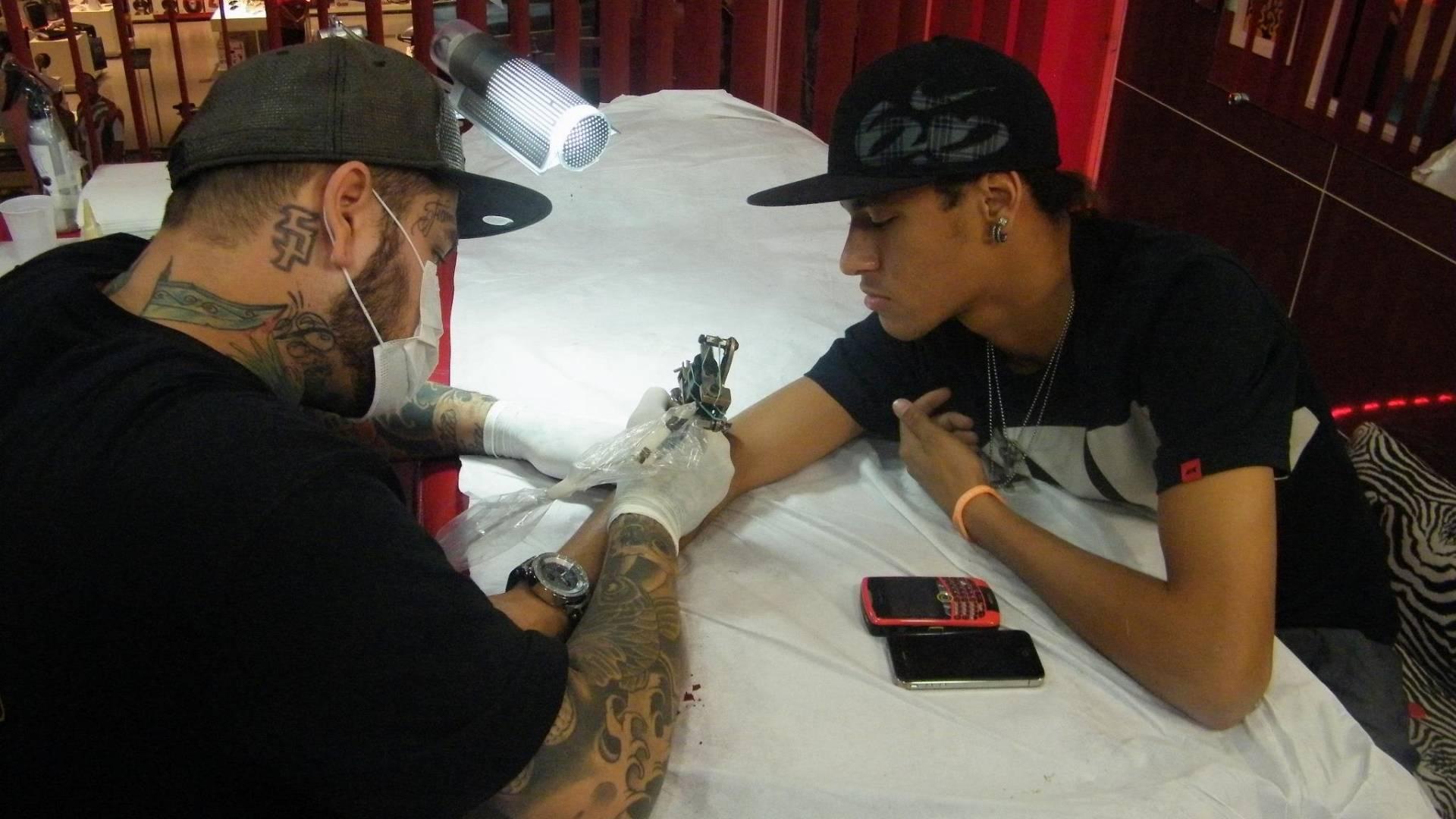 O tatuador Adão Rosa tatua o jogador do Santos, Neymar (30/8/11)