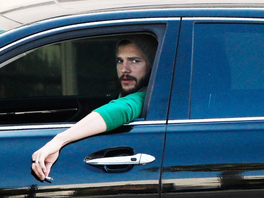 Com um cigarro na mão, Ashton Kuther chega para gravar cenas do seriado