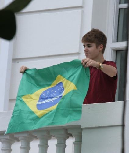 Justin Bieber segura bandeira do Brasil na sacada de hotel em Copacabana