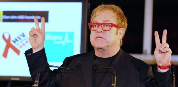 """Elton John faz sinal de """"paz e amor"""" no Dia Mundial de Luta Contra a Aids, em Sydney (1º/12/11) - AFP"""