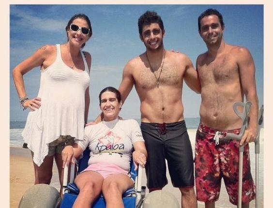 Luana Piovani posta uma foto sua no Twitter com amigos do marido Pedro Scoby que fazem parte de um projeto que leva deficientes físicos para aprenderem a surfar, no Rio de Janeiro (11/3/12)