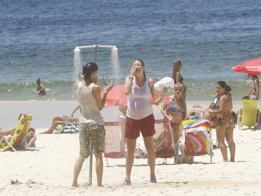 Luana Piovana se refresca tomando banho em um chuveiro na praia do Leblon, zona sul do Rio (1/2/2012)