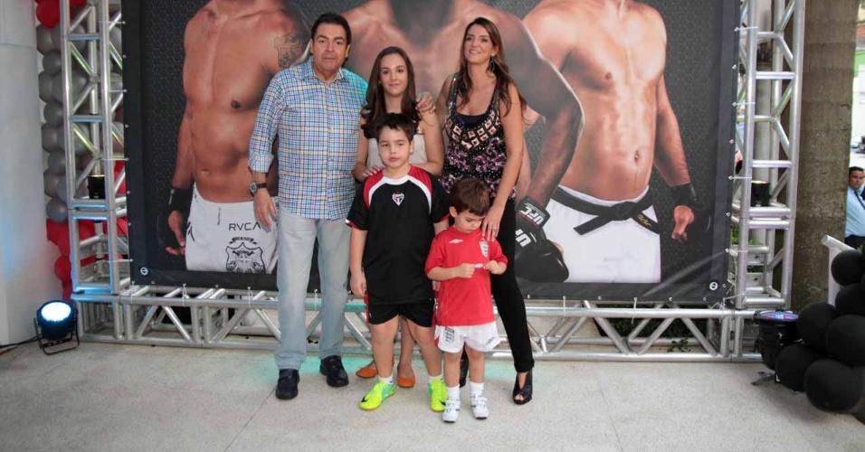 Fausto Silva posa ao lado da família na porta do salão de festas onde é realizado o aniversário de João Guilherme (3/2/2012)