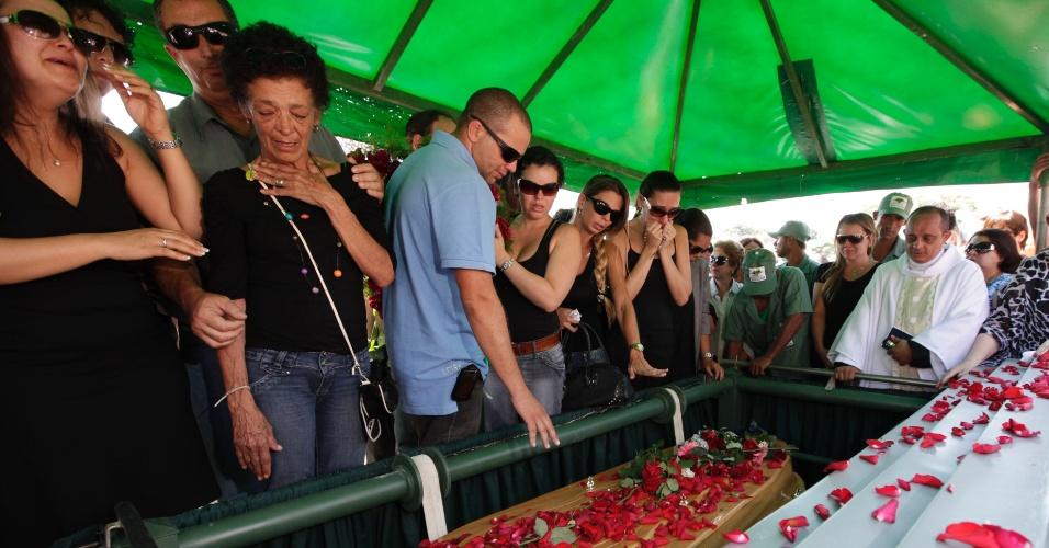"""Ao som de """"Moça"""", o cantor Wando foi enterrado nesta quinta-feira (9), às 11h30, no cemitério Bosque da Esperança, em Belo Horizonte. A cerimônia foi acompanhada por familiares, imprensa e muitos fãs. Estima-se que seis mil pessoas participaram do velório e enterro do cantor. Depois de desmaio, Maria das Graças (colar colorido), irmã de Wando, se despede (9/2/12)"""
