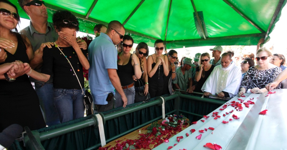 """Ao som de """"Moça"""", o cantor Wando foi enterrado nesta quinta-feira (9), às 11h30, no cemitério Bosque da Esperança, em Belo Horizonte. A cerimônia foi acompanhada por familiares, imprensa e muitos fãs. Estima-se que seis mil pessoas participaram do velório e enterro do cantor. Recuperada, Maria das Graças (colar colorido), irmã de Wando, se despede (9/2/12)"""