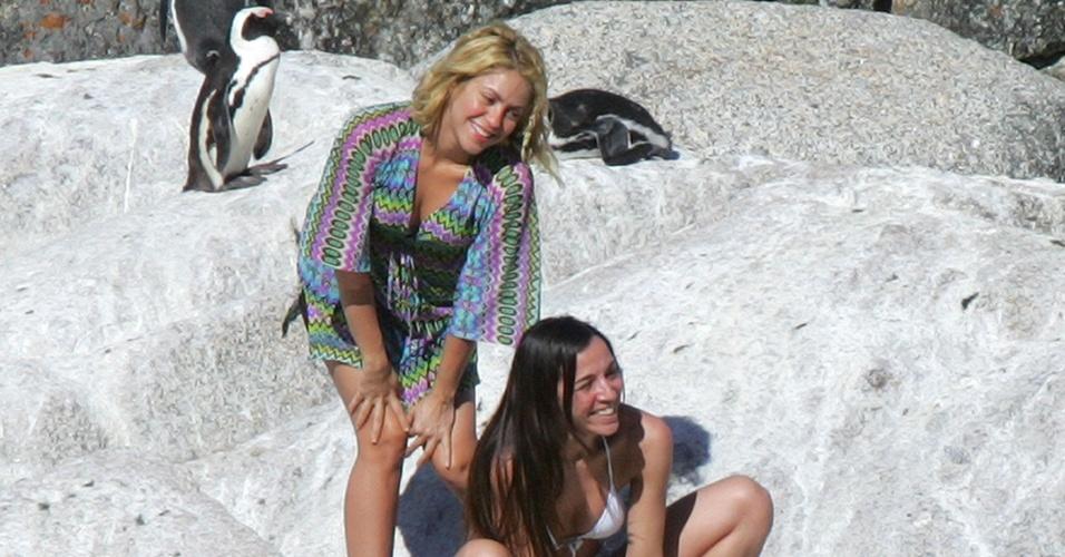 Em Cape Town, na África do Sul, Shakira posa ao lado de pinguins e de amiga.