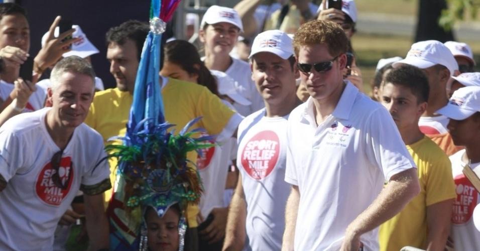 Com uma bandeira do Brasil nas mãos, Harry prepara-se para dar a largada da corrida beneficente (10/3/12)