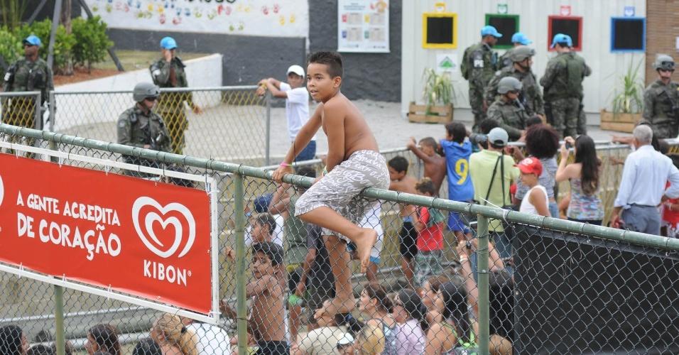 Crianças pulam alambrados de quadra para tentar chegar perto do príncipe Harry no Complexo do Alemão (10/3/12)
