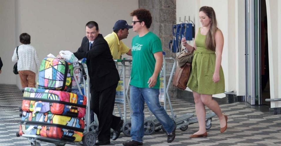 Depois de participar de evento no Morro da Urca, com a presença do príncipe Harry, no Rio de Janeiro, o artista plástico Romero Britto (camisa verde) aterrissa em São Paulo carregado de malas estampadas com seus desenhos (10/3/12)