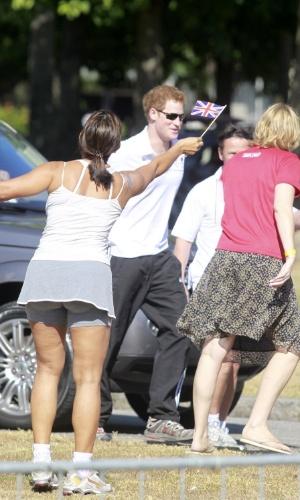 Harry é recebido por fã, que acena uma das 10 mil bandeirinhas distribuídas no evento (10/3/12)
