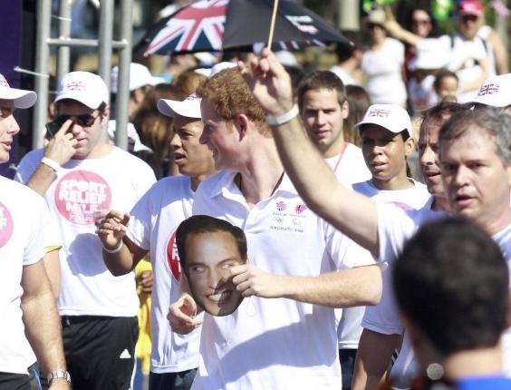 O príncipe Harry ganha uma máscara com a cara do seu irmão, o príncipe William, durante a corrida beneficente (10/3/12)