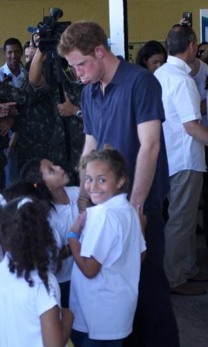 Príncipe Harry faz careta para crianças no Complexo do Alemão, onde foi recebido por um coral formado por crianças da comunidade, no Rio de Janeiro (10/3/12)