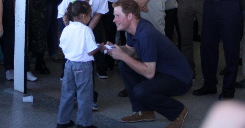 Príncipe Harry ganha presente de menina noComplexo do Alemão, onde é recebido por um coral formado por crianças da comunidade, no Rio de Janeiro (10/3/12)