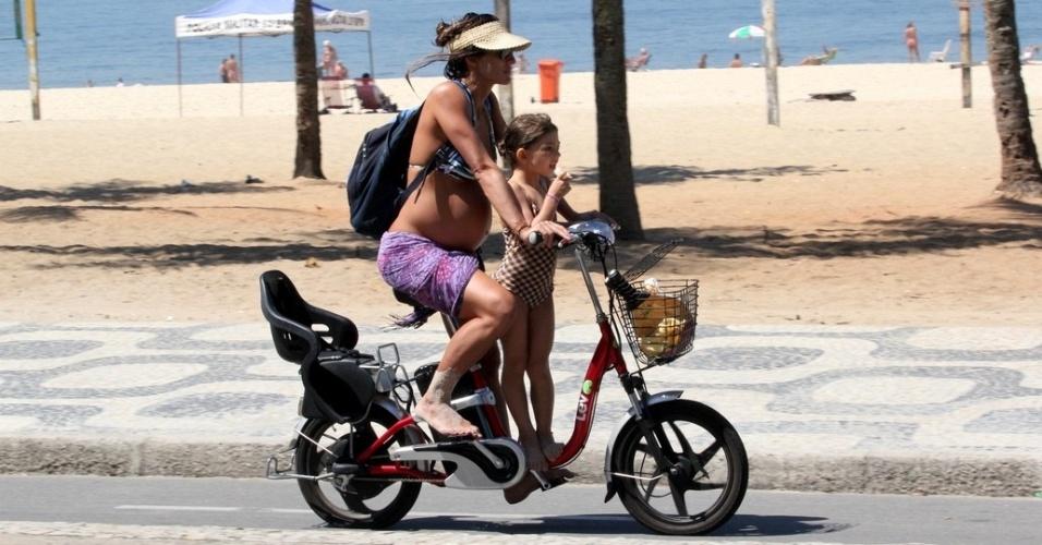 Prestes a dar à luz, Cynthia Howlett passeia de bicleta com a filha na orla de Ipanema (14/3/12)