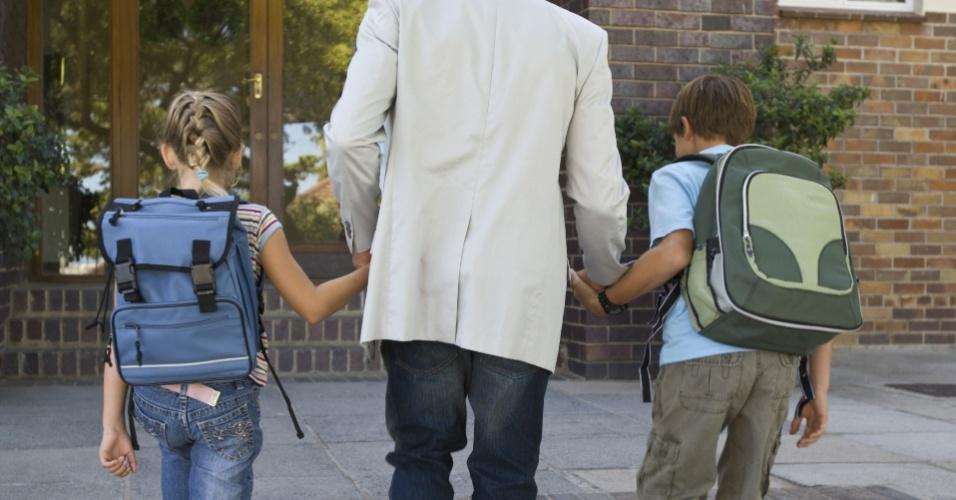 pai levando filhos à escola