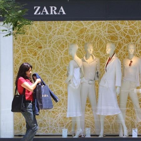 Mulher passa em frente à vitrine de uma loja Zara carregando sacolas da marca - AFP
