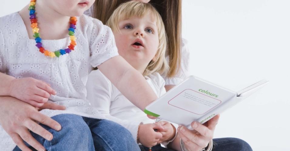 Mãe lendo livro para as filhas
