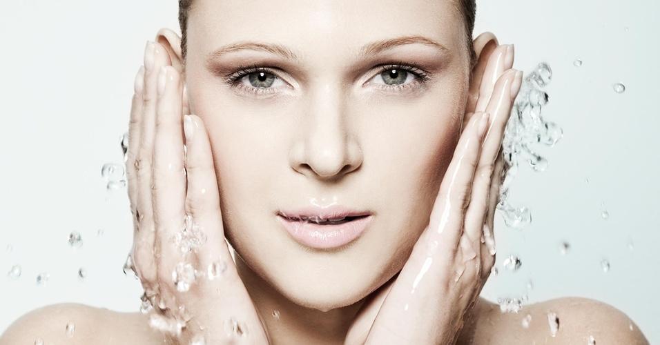 Modelo refresca a pele jogando água no rosto