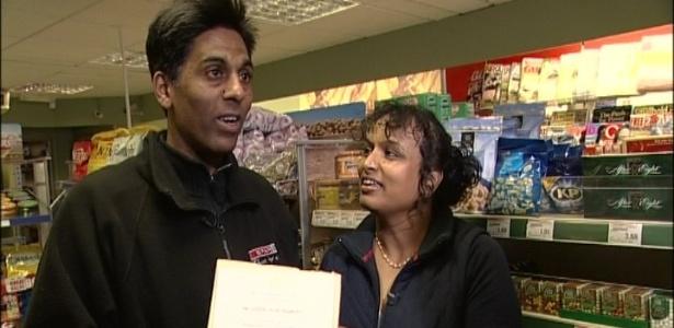 Comerciantes Hash e Chan Shingadia com o convite que receberam para o casamento real - BBC