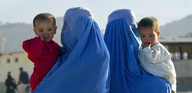Com seus filhos, mulheres afegãs esperam transporte em ponto de ônibus de Cabul  - Reuters