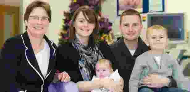 Donna Kelly, de 29 anos, posa com a filha no colo, após passar três meses deitada em uma cama - BBC