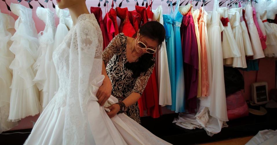 A estilista Yang Lifei faz ajustes em cópia do vestido de noiva de Kate Middleton, na China (05/05/2011)