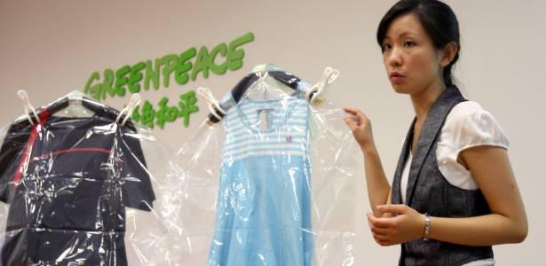 Ativista do Greenpeace mostra roupas de marcas como Adidas, Uniqlo, Calvin Klein, H&M, Abercrombie & Fitch, Lacoste, Converse e Ralph Lauren com resíduos tóxicos  - AFP PHOTO / GREENPEACE
