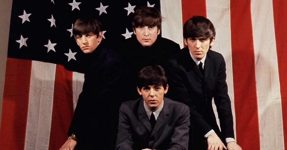 Os integrantes do Beatles Ringo Starr, John Lennon, George Harrison e Paul McCartney posam para foto em frente à bandeira dos Estados Unidos