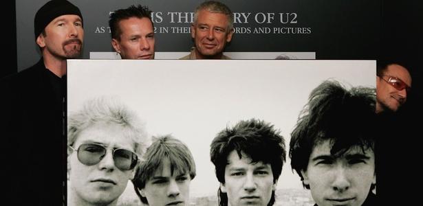 """The Edge, Larry Mullen Jr, Adam Clayton e Bono posam com foto do U2 no começo de carreira em evento de lançamento do livro """"U2 by U2"""", em Londres, Inglaterra (22/09/2006)"""